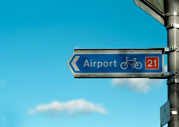 A road sign for the airport with a bicycle icon on it
